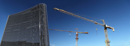 Under construction site building with crane and glass skyscraper. In the blue sky, business success concept Stock Images