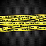 Under construction on tape on metal background Royalty Free Stock Photography