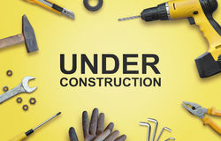 Under construction text surrounded by tools for construction and repair Royalty Free Stock Photos