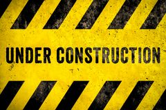 Under construction warning sign text with yellow black stripes painted over concrete wall cement facade texture background. Concept for do not enter the area stock photography