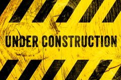 Under construction warning sign text with yellow black stripes painted on wood wall plank texture wide background. Concept do not enter the area, caution royalty free stock images