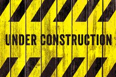 Under construction warning sign text with yellow black stripes painted on wood wall plank texture wide background stock photography