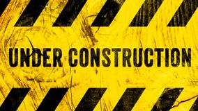 Under construction warning sign text with yellow black stripes painted on wood wall plank texture wide banner panorama background. royalty free stock image