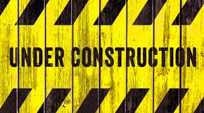 Under construction warning sign text yellow black stripes painted on wood wall plank texture wide panorama background stock photography