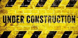 Under construction warning sign with yellow and black stripes on brick wall texture background in wide panorama format. Concept for do not enter the area stock images
