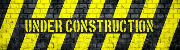 Under construction warning sign with yellow and black stripes on concrete wall texture background wide panorama format. Under construction warning sign with Stock Photos