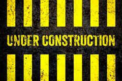 Under construction warning sign with yellow and black stripes painted over cracked concrete wall coarse texture background. Concept for do not enter the area Stock Image
