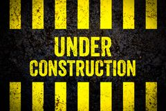 Under construction warning sign with yellow and black stripes painted over cracked concrete wall weathered texture background. Concept for do not enter the royalty free illustration