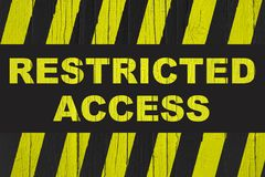 Restricted access text warning sign with yellow and black stripes painted over cracked wood Royalty Free Stock Photography