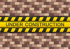 Under construction yellow tape on brickwall Stock Image