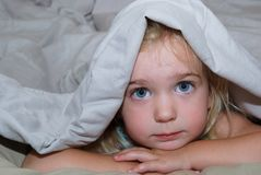 Under cover. Young girl under the covers Stock Photography