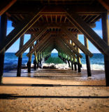 Under the Crystal Pier. A very symmetrical look underneath the Crystal Pier. Wrightsville Beach, NC royalty free stock photos