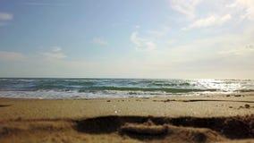 Under den blåa himlen rullar vågorna in på stranden arkivfilmer