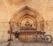 Under den famouseperserPol-e Khaju bron och den aktiva mannen för åldring som läser en bok Royaltyfria Foton