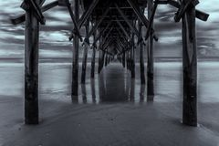 Under the dock at the beach in black and white. Long exposure in black and white Under the dock at the beach with dramatic sky Royalty Free Stock Photo