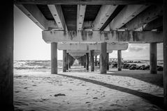 Under the dock, BN, Palanga, Lithuania. BW photo in Palanga Beach, under the dock, cold water, strong wind and beautifull light Stock Photos