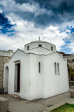 A small white chapel in central square of town Skyros. Sporades islands. Greece. Under a dramatic sky a small white chapel in central square of town Skyros Royalty Free Stock Photos