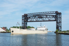 Under The Drawbridge. A Great Lakes bulk carrier freighter laden with powdered cement passes under the Norfolk Southern Railway drawbridge as it sails up the royalty free stock images