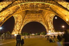 Under the Eiffel Tower illuminated at night Stock Photography