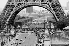Under the Eiffel Tower, Paris. Paris, France - 5 October 2014.nTourists and citizens of Paris are walking under the Eiffel Tower. Black and white photo Stock Images