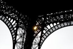 Under the Eiffel tower - wrought iron silouette. Bright sun shining through wrought iron silhouette stock photography