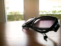 Under expose of fashion sunglasses on the wooden table Stock Photo