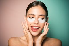 Under eye patches for dark circles and puffiness. Taking care of her skin. Pretty woman using eye patches spending time. At home. Daily pampering routine royalty free stock photo