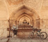 Under famouse persian Pol-e Khaju bridge and elderly active man reading a book. ISFAHAN, IRAN - OCT 14: Under famouse persian Pol-e Khaju bridge and elderly royalty free stock photos