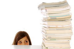 Under the gaze of culture. A girl under the stern gaze of a stack of books Royalty Free Stock Photo