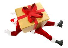 Under giftbox. Photo of tired Santa Claus with big giftbox on his back royalty free stock photo