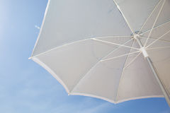 Under a grey beach umbrella looking up into the opened parasol against a blue sunny sky Stock Photography