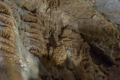 Under the ground. Beautiful view of stalactites and stalagmites in an underground cavern - New Athos Cave. Sacred stock photos