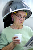 Under the Hair Dryer. Senior woman reading the newspaper and drinking coffee while under the hair dryer at the beauty parlor Royalty Free Stock Photo