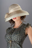 Under the hat. A portrait of an elegant pretty woman hiding her eyes under a beige vintage hat Royalty Free Stock Photos