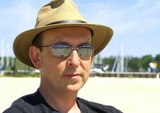 Under a Hat on the Beach. A man enjoys a sunny day on the beach wearing a hat and sunglasses stock images