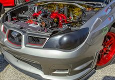 Under the hood of a car on exhibit with grey and red parts Stock Photo