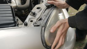 Under the hood of the car a man puts a spotlight in a car service. Under the hood of the car  a man puts a spotlight in a car service stock footage