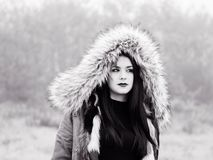 Under hood teen girl looking away. Under hood cold weather teenager girl outdoors foggy day forest isolated b&w Stock Photo