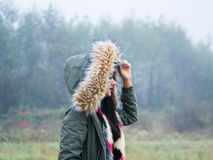 Under hood teen girl walking. Under hood cold weather teen girl outdoors foggy day forest isolated walking Stock Image