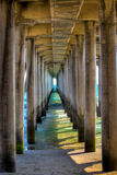 Under the Huntington Beach Pier. Looking out toward the sea while standing under the pilings of the Huntington Beach Pier in Huntington, CA Royalty Free Stock Image