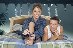 Under icicles bed. Young couple in bed with icecles and fir background stock photography
