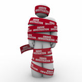 Under Investigation Words Red Tape Around Man Crime Suspect Arre. Under Investigation words on red tape wrapped around a man or person suspected of a crime and Stock Photos