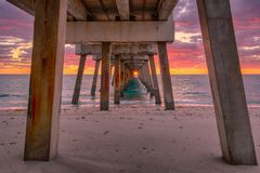Under Juno Beach pier. Spectactular sunrise at Juno Beach pier in Florida. The pilings frame the sunrise on Earth day royalty free stock photo