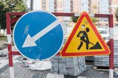 Under konstruktionsteckencloseupen Vägarbeten undertecknar för byggnationer i stadsgata på en trottoarväg reparera royaltyfria bilder