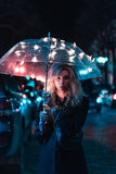 Under the light of an umbrella. On a night street Stock Images
