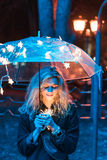 Under the light of an umbrella. On a night street Stock Photography