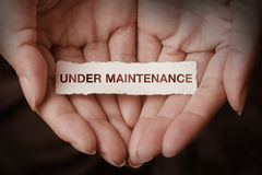 Under maintenance text on hand Royalty Free Stock Images