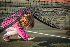 Under the net. Little girl crawling under the net on the tennis court Stock Photos