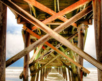 Under the Pier. Crossbeams under the Cherry Grove Pier in South Carolina with storm clouds in the background Royalty Free Stock Photo