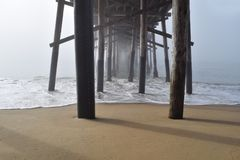 Under a Pier in the Fog. The underside of Balboa Pier appears to stretch into eternity this foggy morning in Newport Beach California stock photography